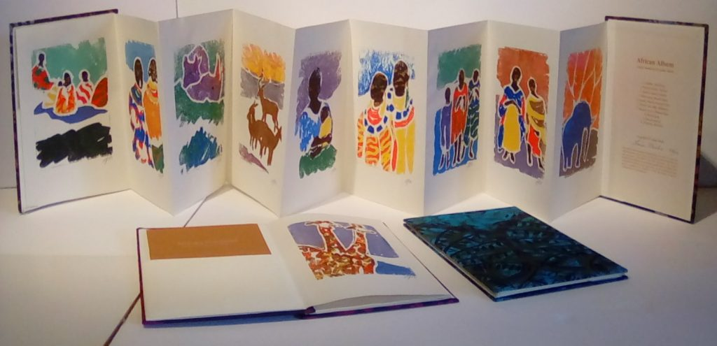 A series of artistic illustrations of African traditions on the pages of a book