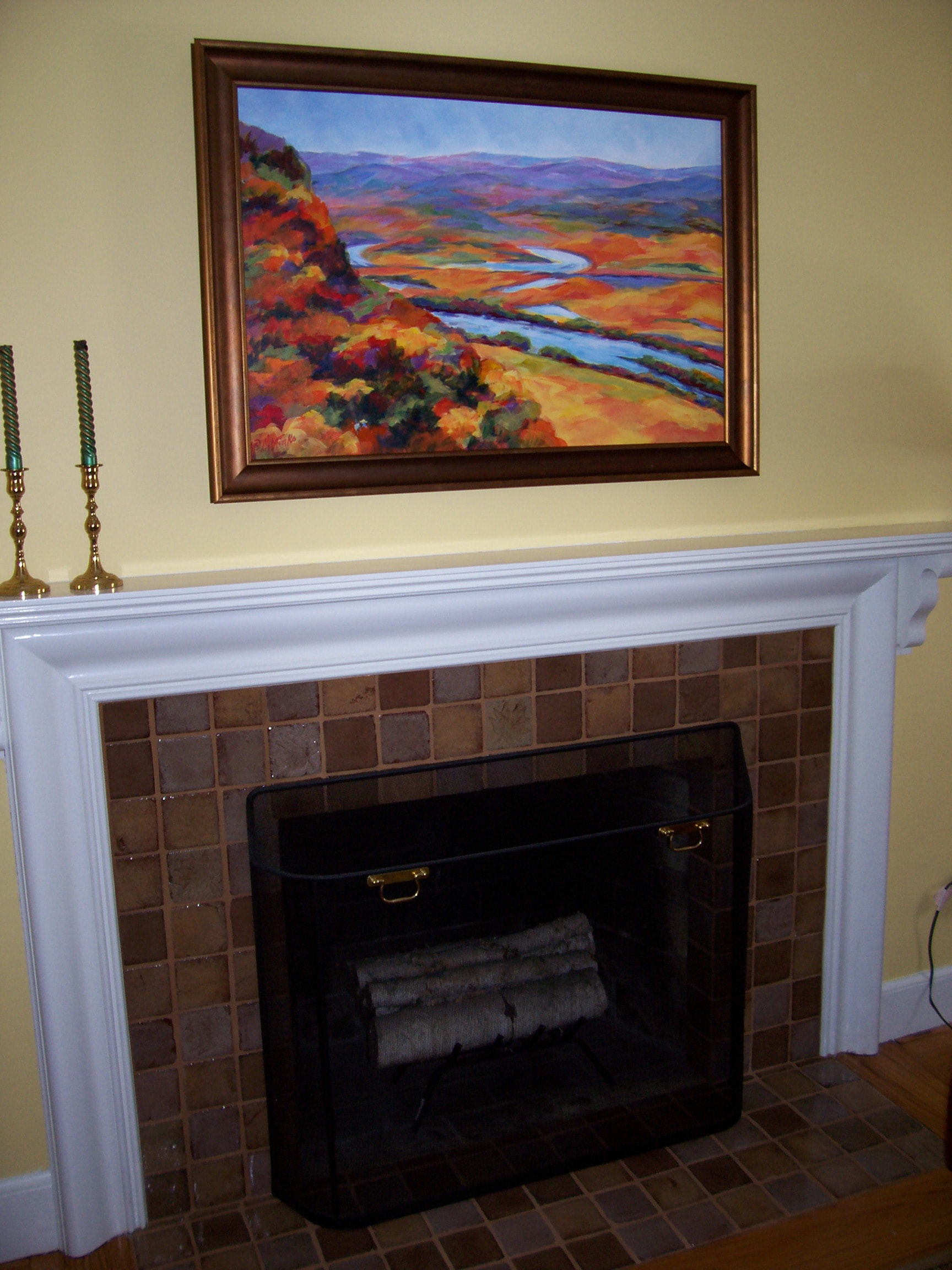 A painting of an aerial view of a river winding through a hilly autumn landscape above a fireplace