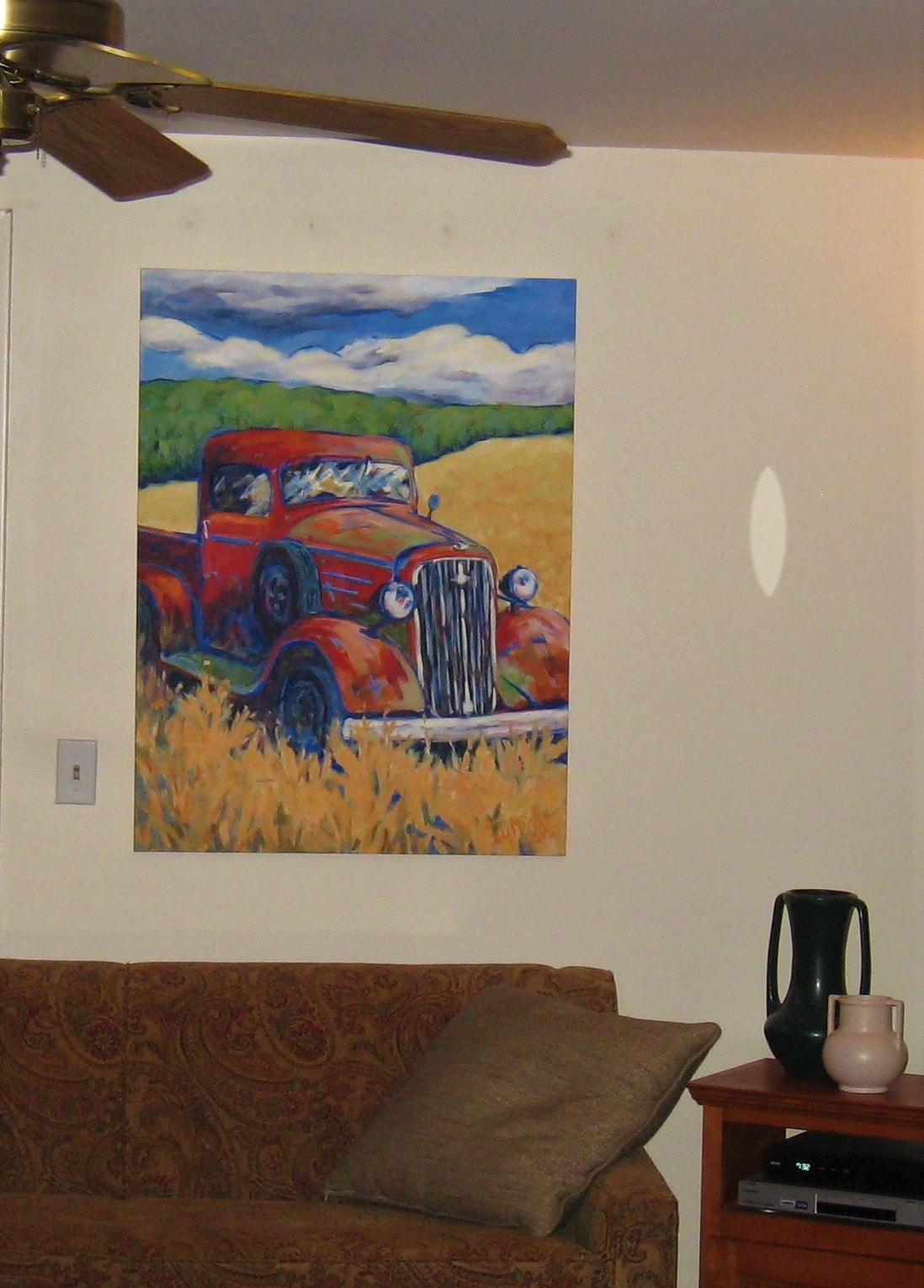 A painting of a red truck in a field displayed over a couch in a home