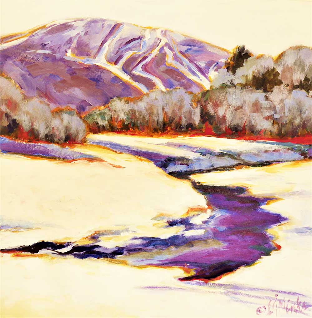 A river cuts through a snowy landscape while a mountain with ski trails rises in the distance